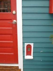 A tiny red door next to a large red front door